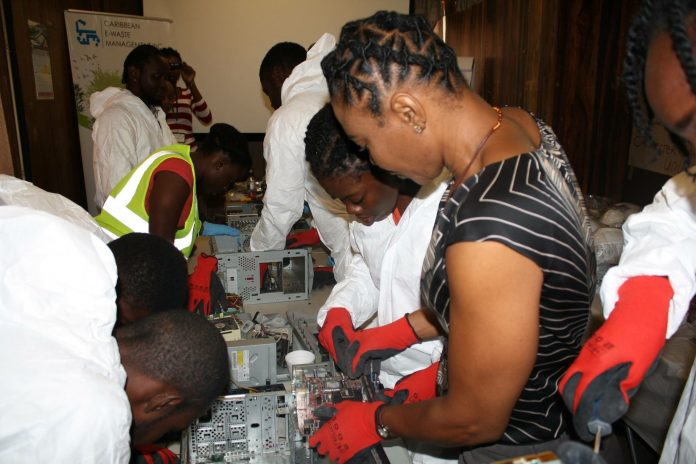 Malikca Cummings and workers taking apart machines to find recyclable material (Courtesy of Malikca Cummings)