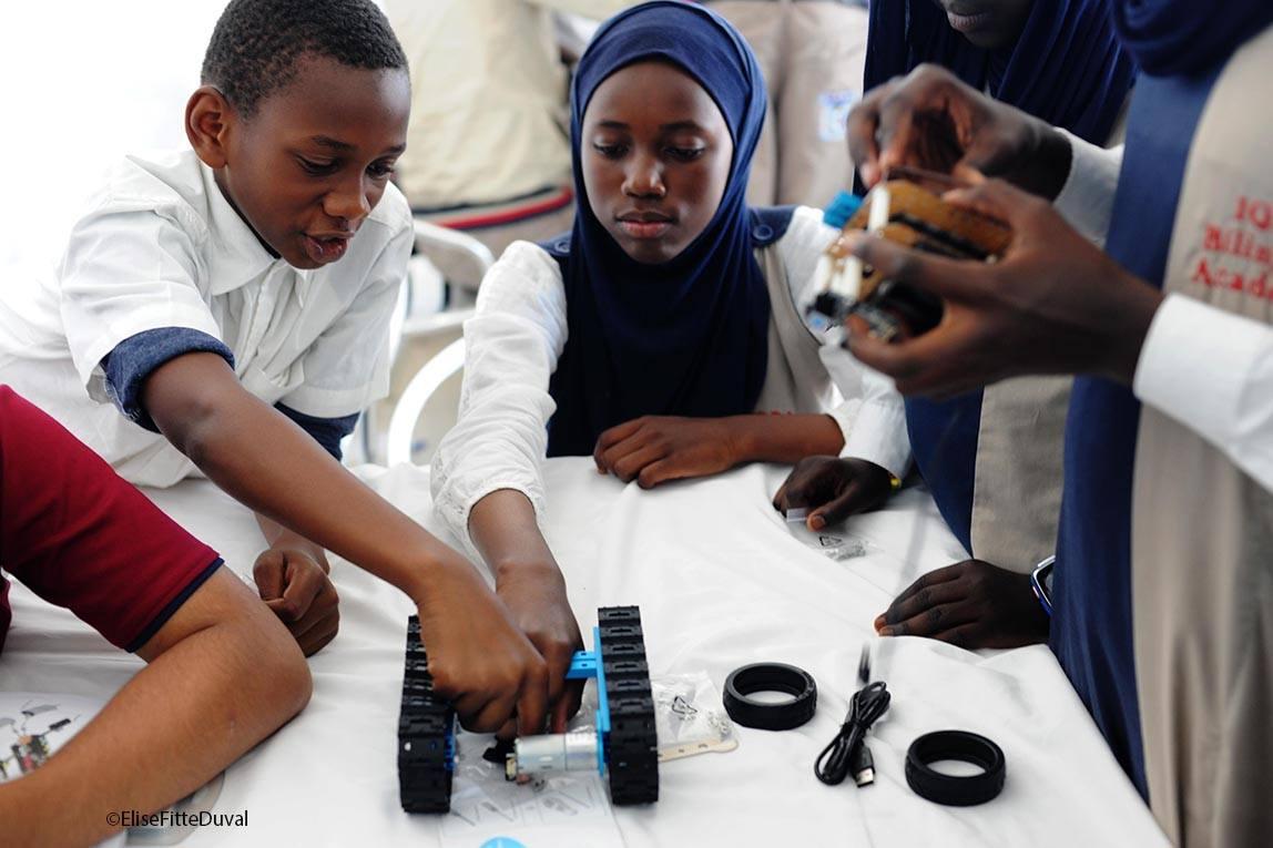 Un garçon et une fille tiennent une pièce détachée d'un robot. (@EliseFitteDuval)