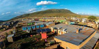 Vue aérienne d'un village avec une machine équipée de panneaux solaires sur un terrain (© Sameer Halai, SunFunder)