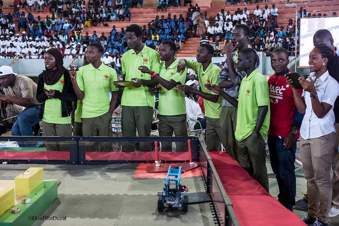 Un groupe de jeunes habillés de la même manière, rassemblés autour d'un support sur lequel circule un robot. (@EliseFitteDuval)