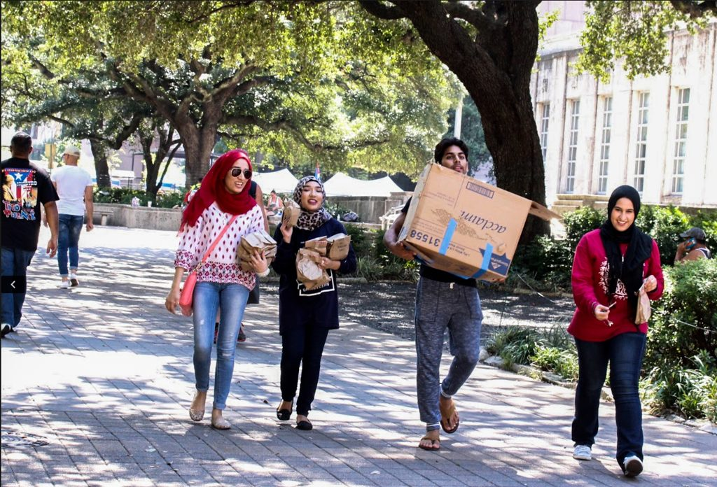 Three women wearing hijabs and man carrying boxes and packages (Courtesy of Islamic Relief USA)