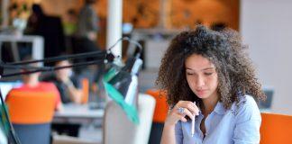 Wanita muda duduk di meja di kantor (Shutterstock)