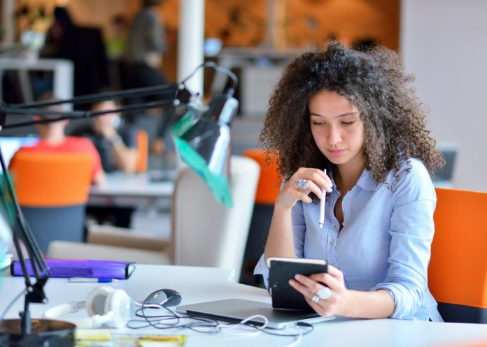 Young woman sitting at desk in office (Shutterstock)