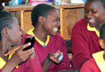 Smiling students holding mobile phones (Courtesy of Eneza Education)