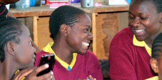 Estudiantes sonrientes con teléfonos móviles en las manos (Foto cedida por Eneza Education)