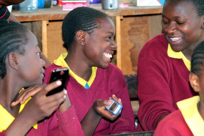 Улыбающиеся школьники держат мобильные телефоны (Courtesy of Eneza Education)