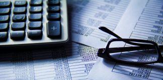 Gros plan sur une calculatrice, des papiers remplis de chiffres, et une pair de lunettes (@ Reynermedia)