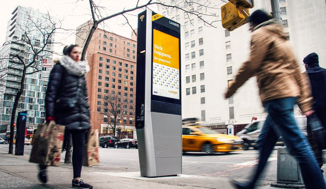 People walking by LinkNYC kiosk on sidewalk (Courtesy of CityBridge)