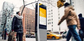 People walking by LinkNYC kiosk on sidewalk (Courtesy of CityBridge)