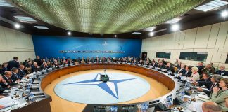 People sitting at round conference table around NATO symbol (© NATO)