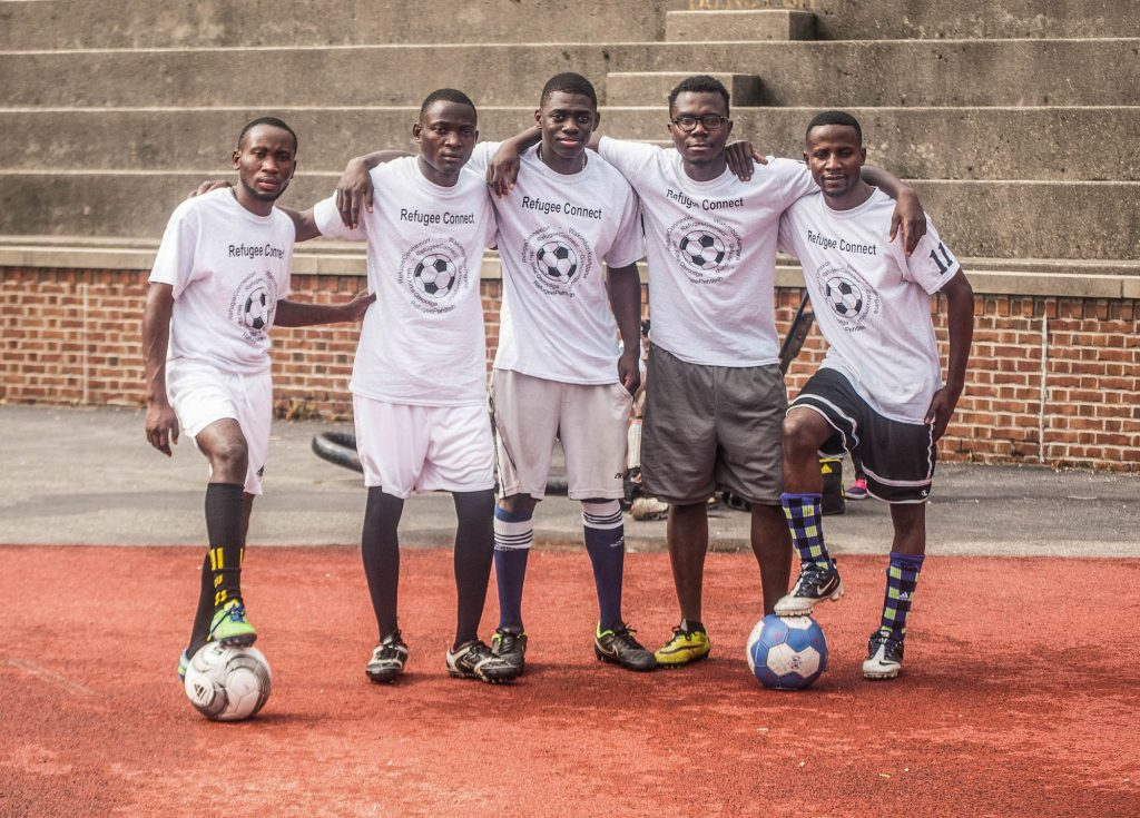 Group of soccer players standing together with soccer balls (© Dyah K. Miller/Arteologie)