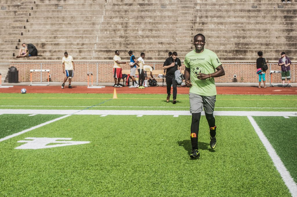 Man running and smiling on sports field (© Dyah K. Miller/Arteologie)