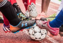 Feet wearing athletic shoes resting on soccer ball (© Dyah K. Miller/Arteologie)