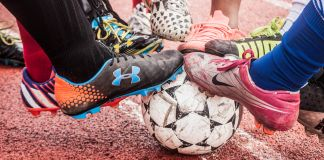 Feet wearing athletic shoes resting on soccer ball (© Dyah K. Miller/Arteologie)