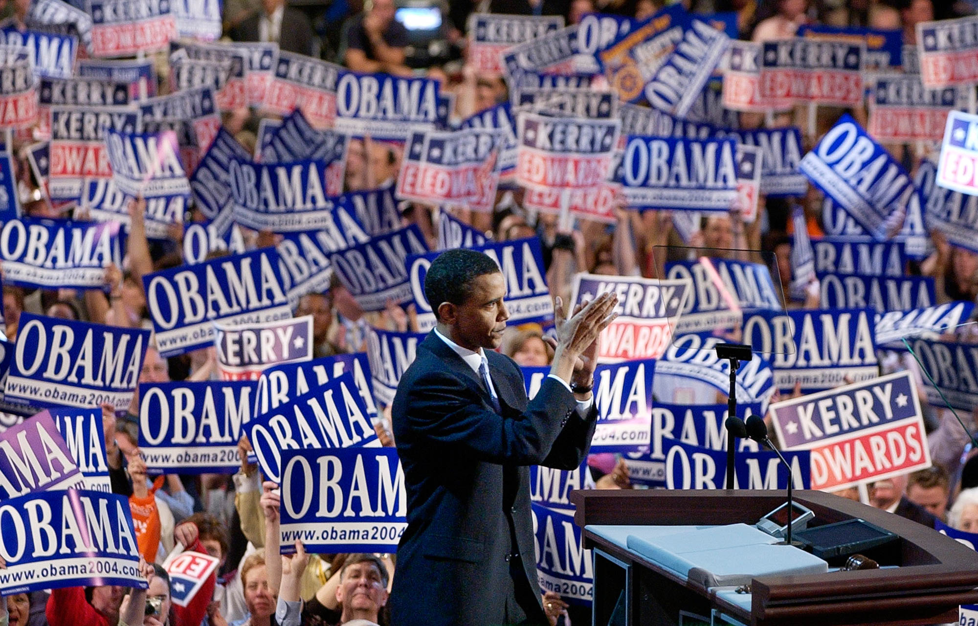 Then-Senate candidate Barack Obama speaking at 2004 Democratic National Convention; crowd holding placards in background (© AP Images)