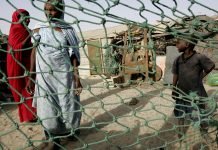 Poor Mauritanians behind cyclone fencing (© AP Images)