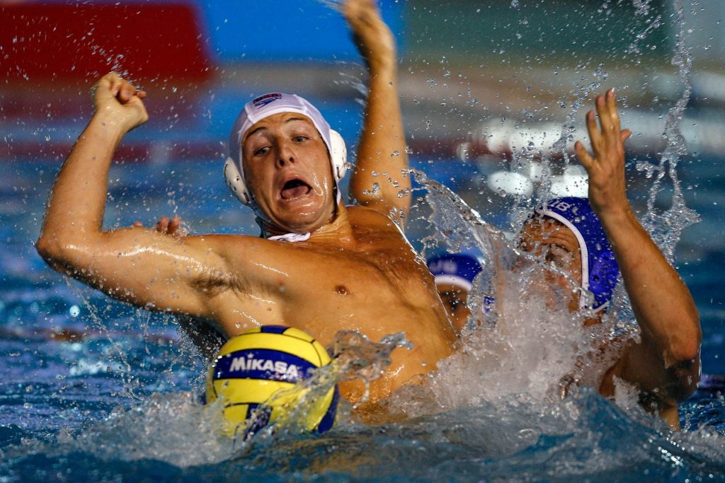 Men in pool playing water polo (© AP Images)