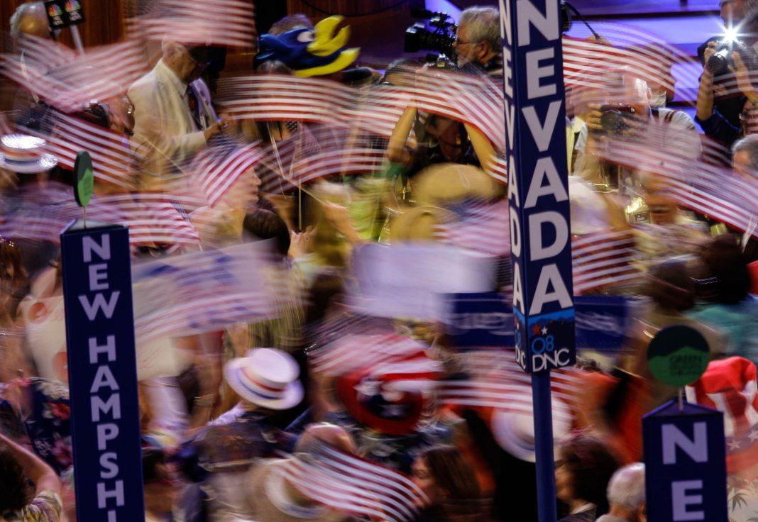 Une photo floue d'une foule, de drapeaux agités et des panneaux au premier plan (© AP Images)