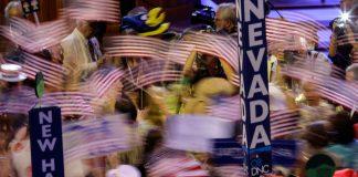 Personas reunidas levantando carteles y ondeando banderas (© AP Images)
