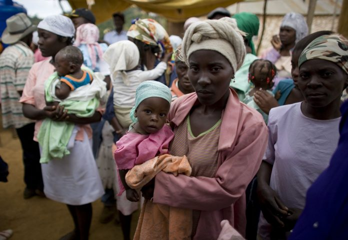 Women standing in a line holding their children. (© AP Images)
