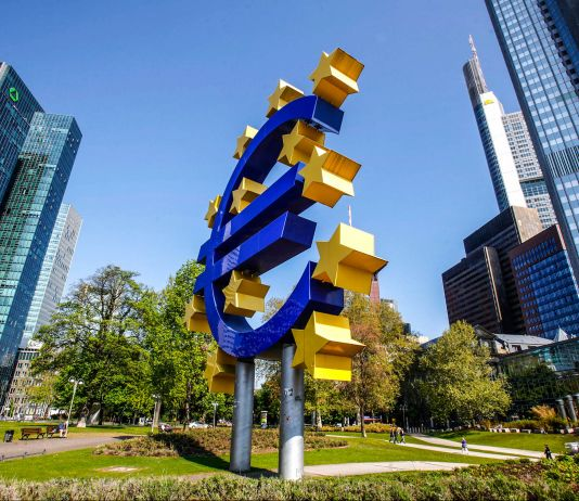 Trees and buildings surrounding the Euro symbol sculpture (© AP Images)