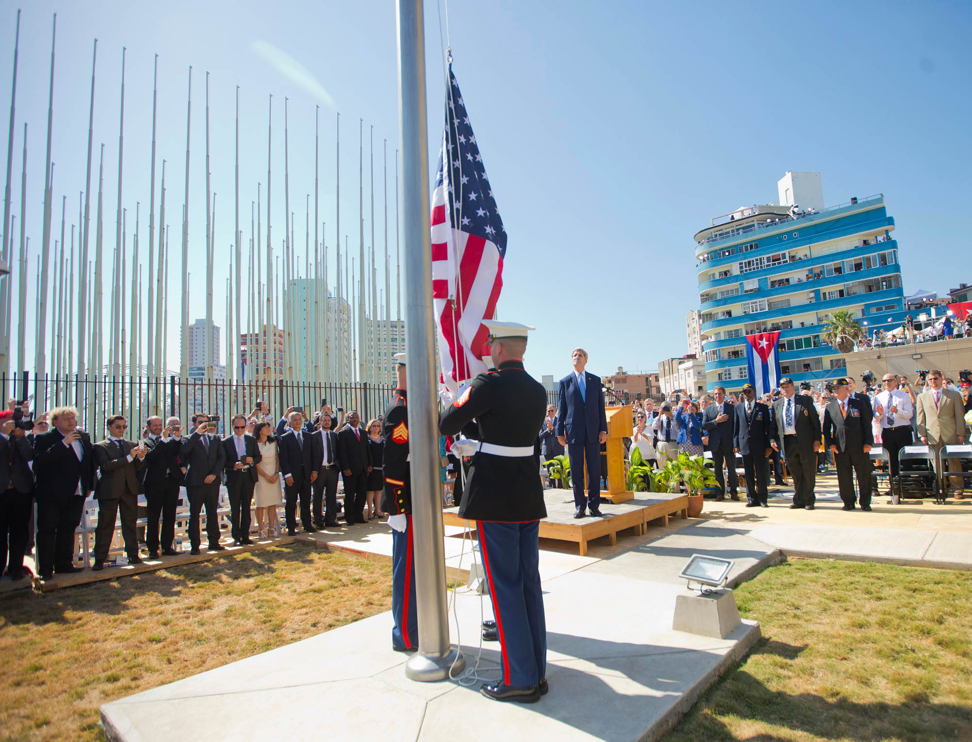 John Kerry, marines and other people looking at the U.S. flag (© AP Images)
