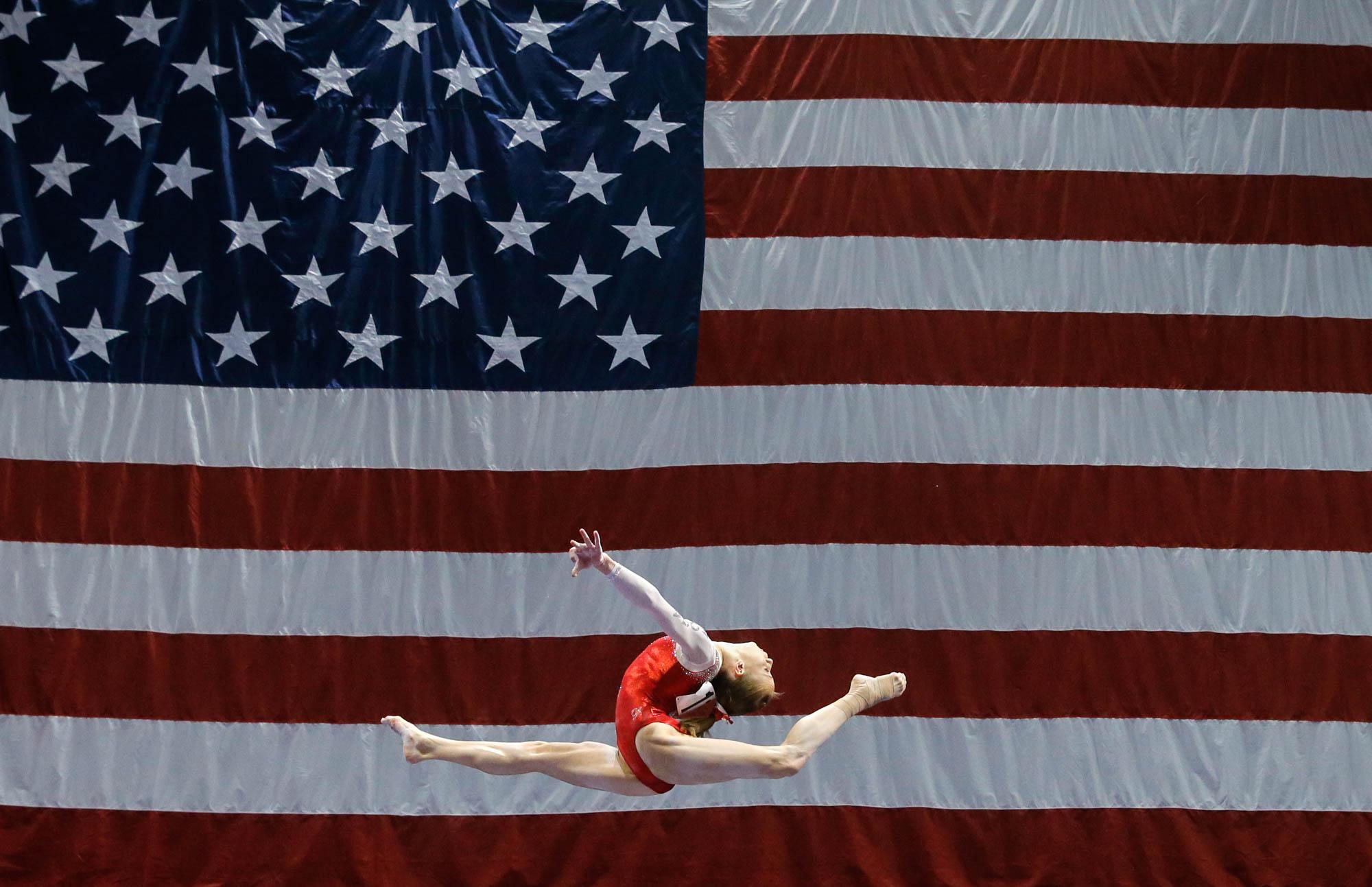 Madison Kocian haciendo un salto. Al fondo, la bandera de Estados Unidos (© AP Images)