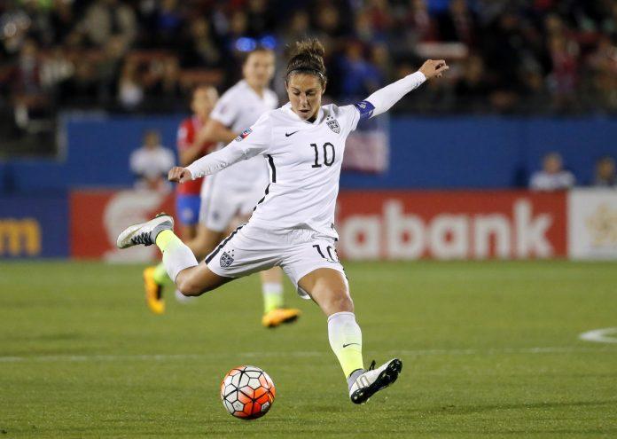 Carli Lloyd chuta uma bola em uma partida de futebol (© AP Images)