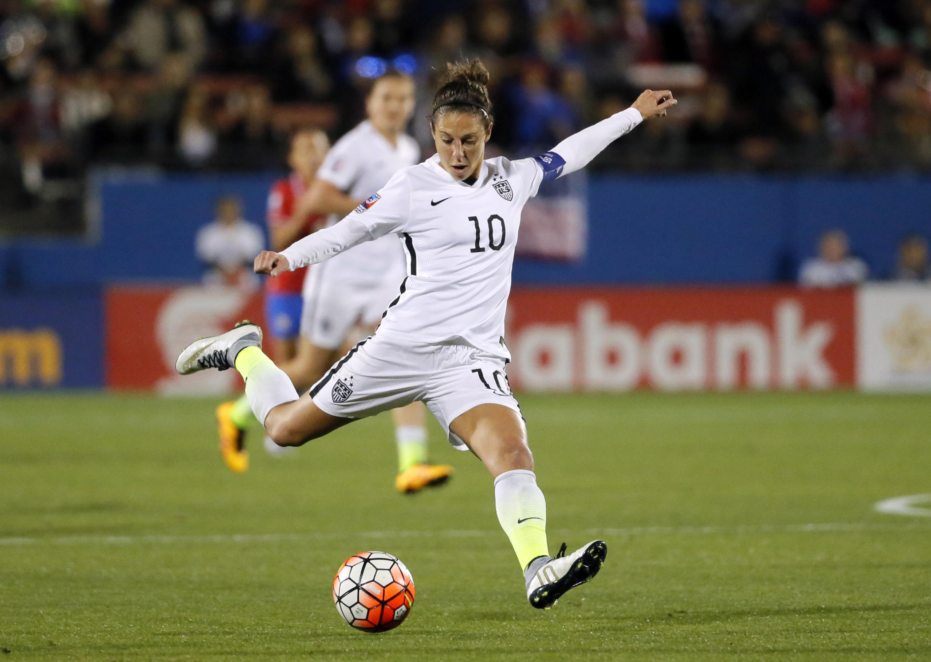 Carli Lloyd kicking soccer ball during game (© AP Images)