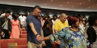 Personas de distintas razas sujetas de la mano con la cabeza inclinada hacia adelante en un gran salón (© AP Images)