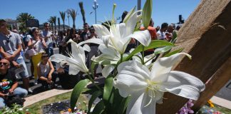 Crowd surrounding flowers in vigil for victims (© AP Images)