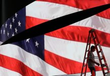 U.S. flag and a man with a ladder (© AP Images)