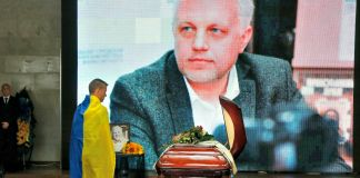 Man draped in Ukrainian flag standing at coffin with image of Pavel Sheremet displayed in background (© AP Images)