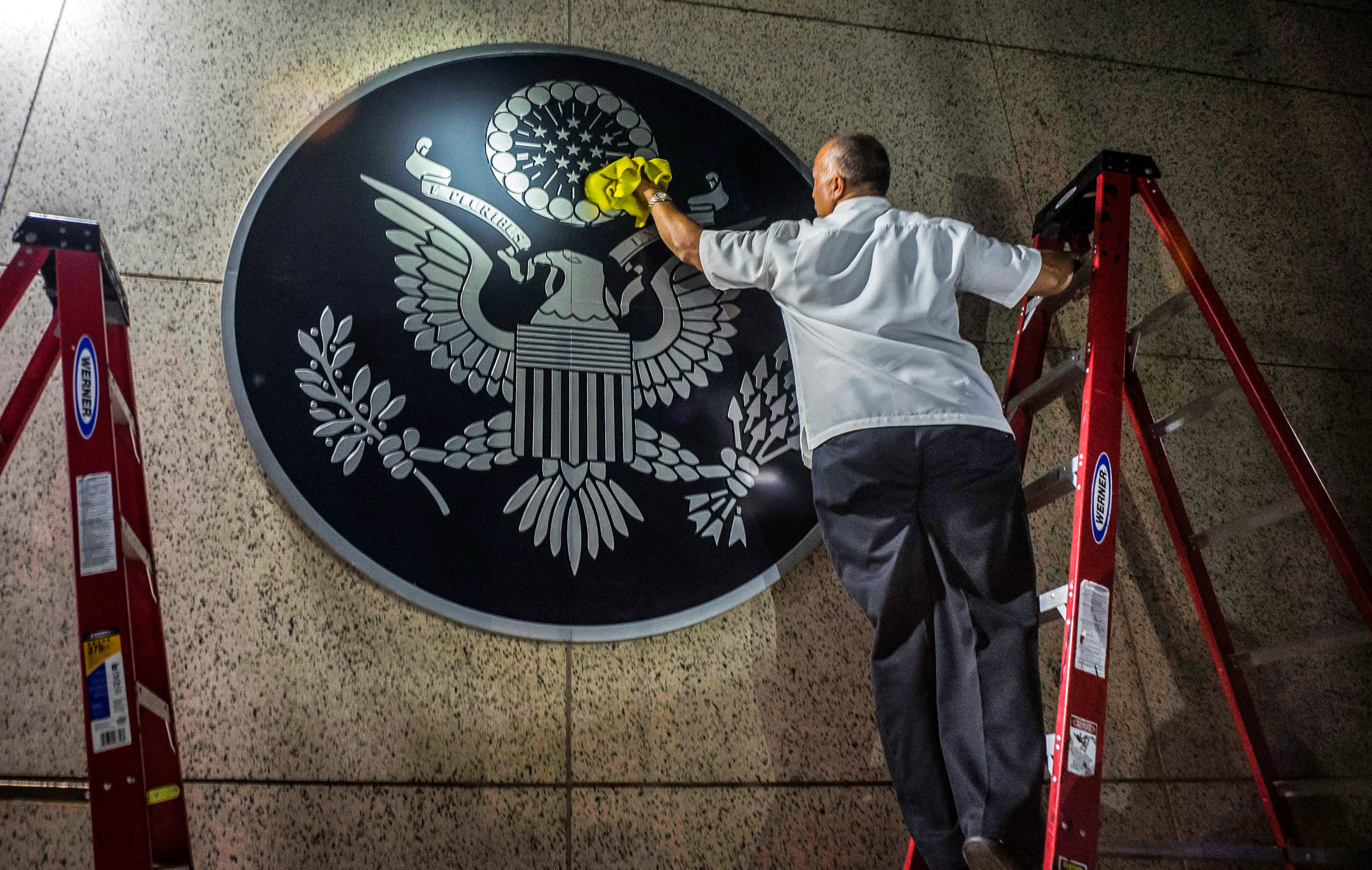 Man on ladder dusting wall decoration (© AP Images)