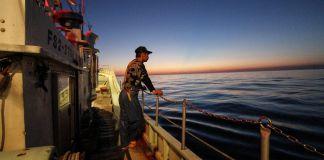 Hombre en un bote contemplando el agua al atardecer (© AP Images)