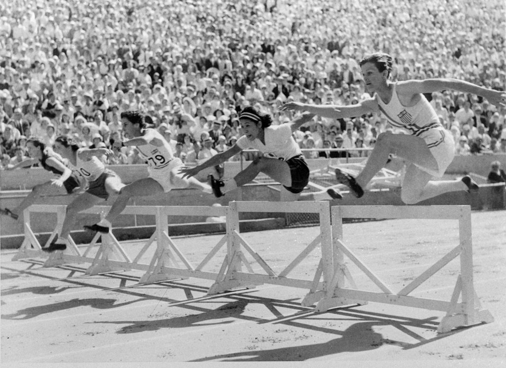 Babe Didrikson and others clearing hurdles in race (© AP Images)