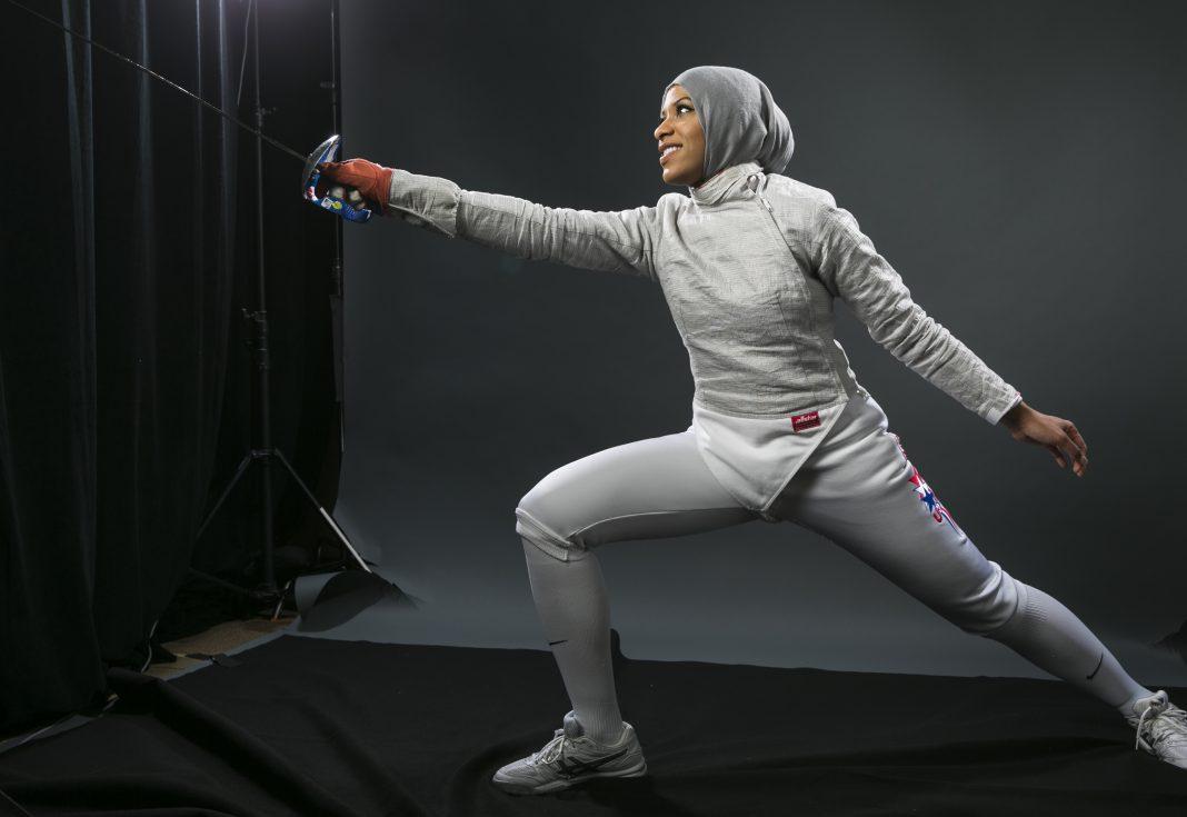 Ibtihaj Muhammad holding sabre and lunging (© AP Images)