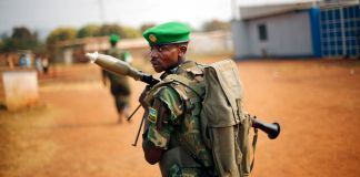 African Union soldier wearing green beret, carrying grenade launcher (© AP Images)