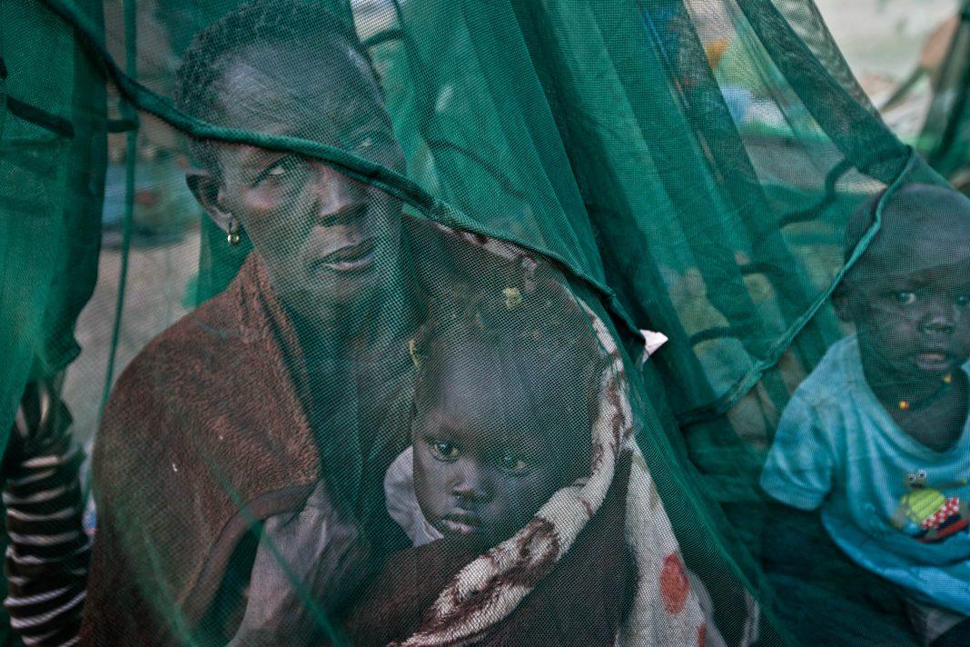 Una mujer y su hijo bajo un mosquitero (© AP Images)