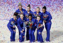 U.S. women's gynmastics team posing for photo with flowers and confetti (© AP Images)