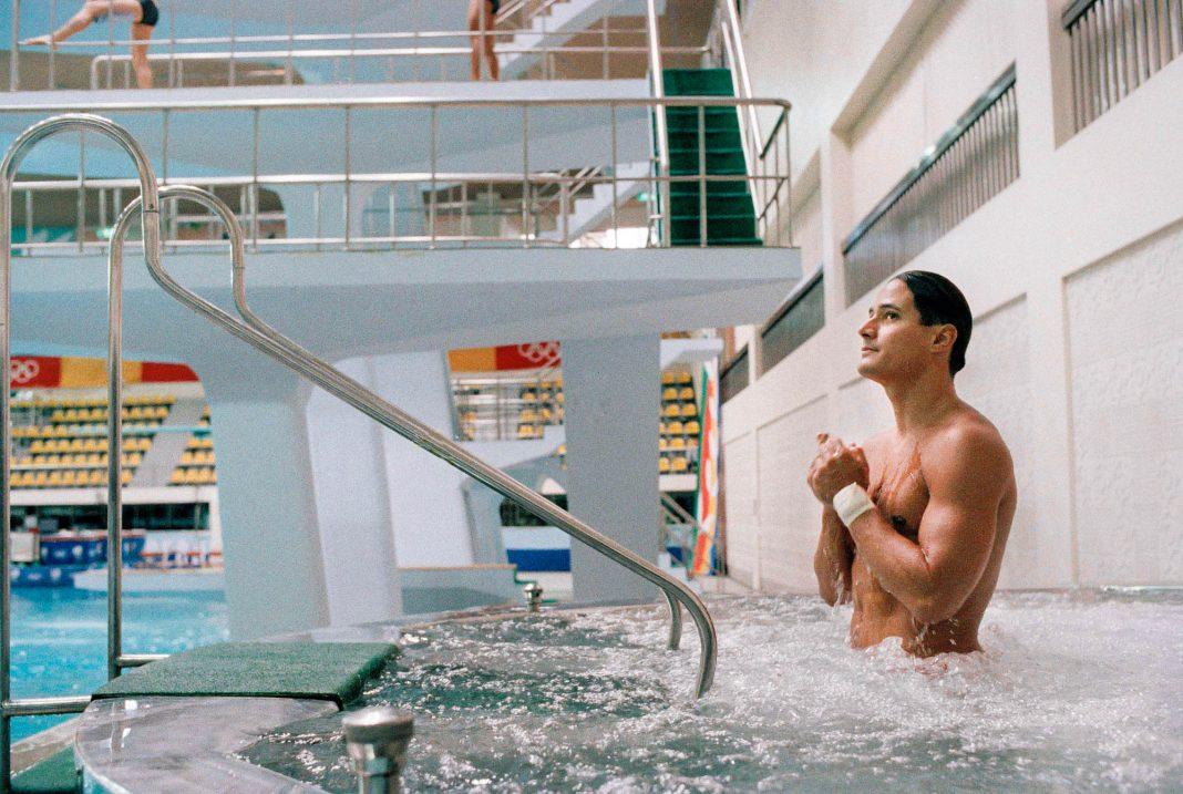 Greg Louganis standing in pool (© AP Images)
