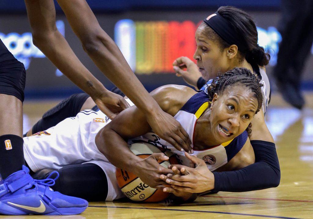 Tamika Catchings y Maya Moore luchan por la pelota de baloncesto (© AP Images)