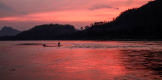 People boating on river at sunset (© AP Images)