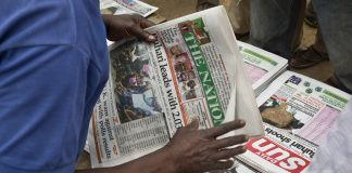 Hands holding newspaper at newsstand (© AP Images)