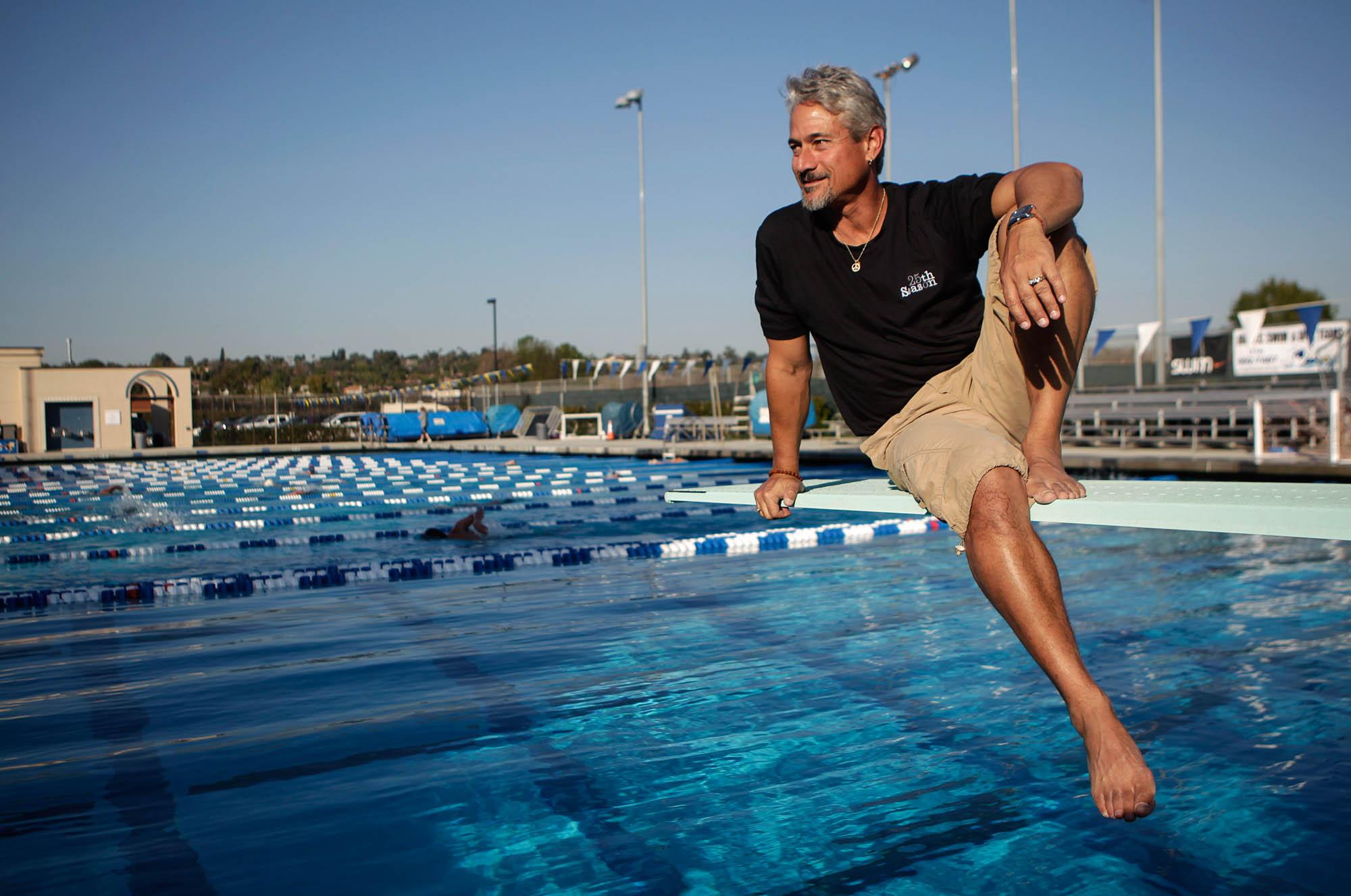 Greg Louganis sitting on pool diving board (© AP Images)