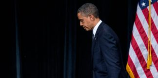President Obama walking off stage with bowed head (© AP Images)