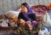 Mujer sentada con niña durmiendo en su regazo (© AP Images)