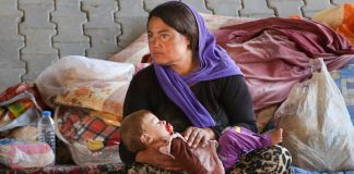 Woman sitting holding sleeping child in her lap (© AP Images)