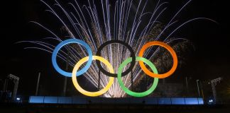 Olympic rings in front of fireworks (© AP Images)