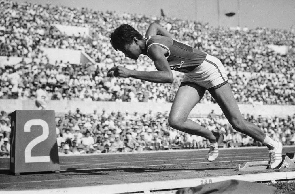 Wilma Rudolph racing in front of large crowd (© AP Images)